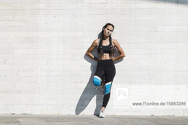 Ganzkörperporträt einer Athletin  die an einer Betonwand lehnt