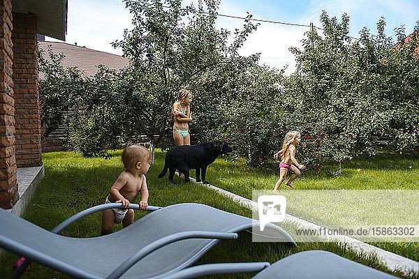 Kleines Mädchen spielt mit Wasser im Hof eines Hauses mit einem schwarzen Hund
