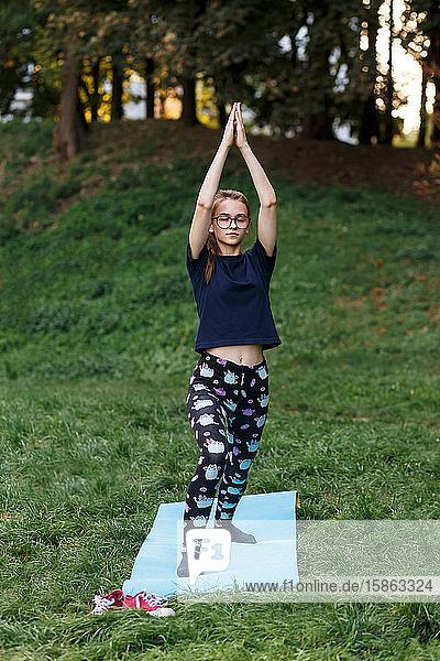 Das entspannte Mädchen macht Yoga im Park auf einem Teppich
