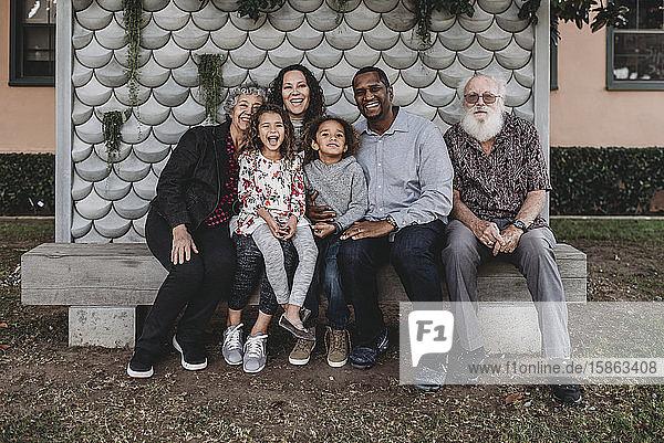 Porträt einer Mehrgenerationen-Familie  die auf einer Parkbank im Freien sitzt