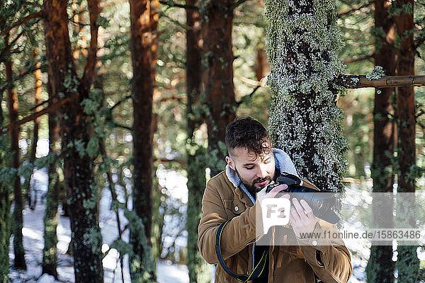 Tourist in den Bergen ruht sich mit seiner Kamera aus
