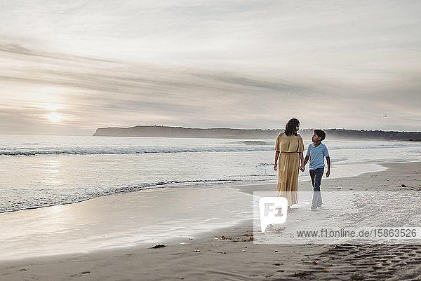 Junge Mutter mit Kleid und Sohn gehen bei bewölktem Sonnenuntergang am Strand