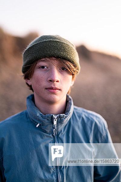 Portrait of teenage boy wearing beenie standing on beach