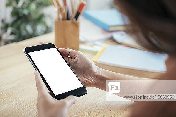 Nahaufnahme der Hand eines Mannes  der ein Smartphone hält.
