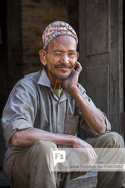 A man in a traditional hat poses for a portrait in Kathmandu  Nepal