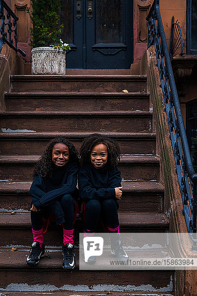 Portrait of confident sisters in sports clothing sitting on steps