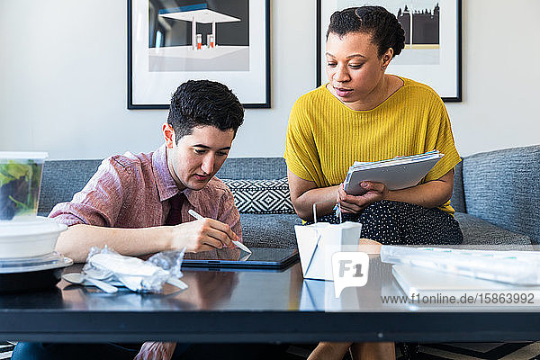 Geschäftsfrau betrachtet einen männlichen Kollegen am Grafiktablett  während sie im Büro am Tisch sitzt