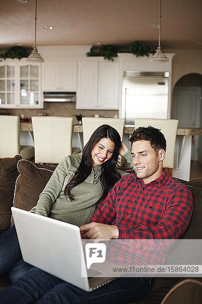 Ehepaar mit Laptop im Wohnzimmer