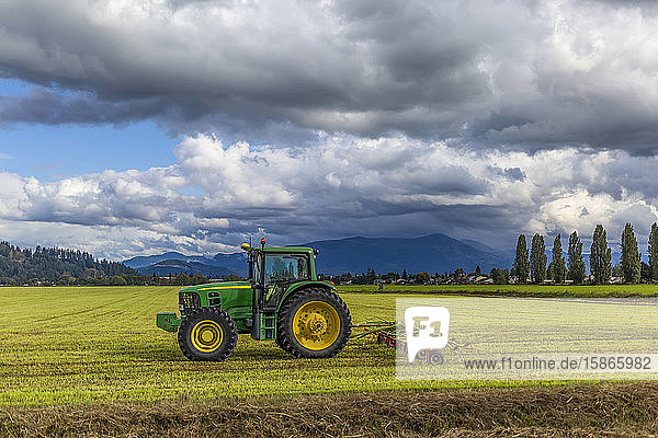 Tractor with implement on farmland and storm clouds over the mountains; Washington  United States of America