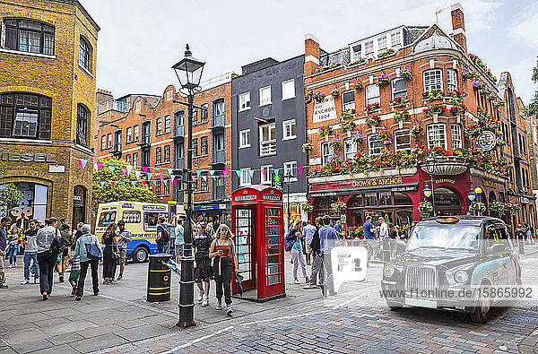Busy street scene and city life on a street corner with red telephone booth; London  England
