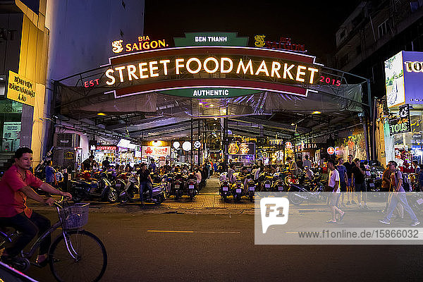 Street Food Market illuminated at nighttime with motorcycles and people outside by the street; Ho Chi Minh City  Vietnam