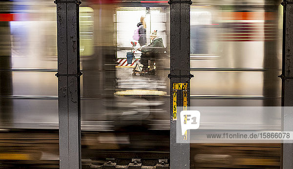 Senior man in scooter viewed through a subway window with the blur from the speed of subway  Manhattan; New York City  New York  USA