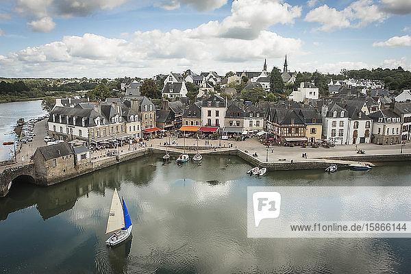 A small sailing boat with a blue and white sail approaches the harbour of Saint Gustan  an old port town with traditional buildings; Saint Gustan  Brittany  France