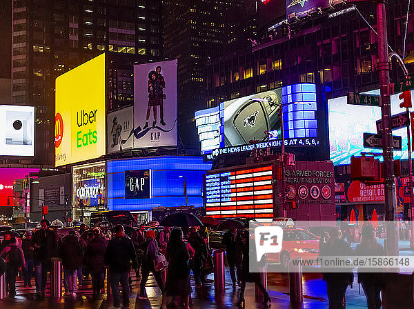 Times Square advertisements illuminated at night with tourists lining the street  Midtown Manhattan; New York City  New York  United States of America