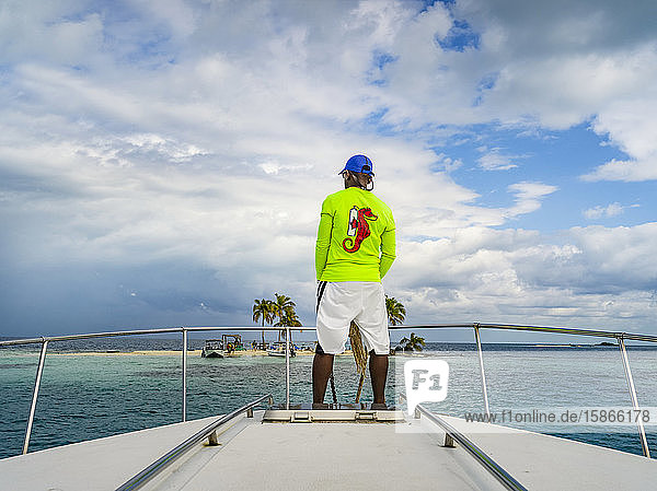 A man rides on the bow of a boat towards a small island with white sand and palm trees in the Caribbean Ocean; Belize
