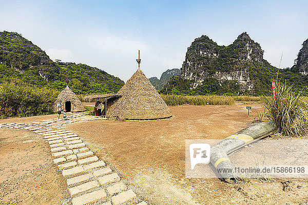 Tourists at thatch structures and limestone karsts  Ninh Binh landscape; Ninh Binh Province  Vietnam