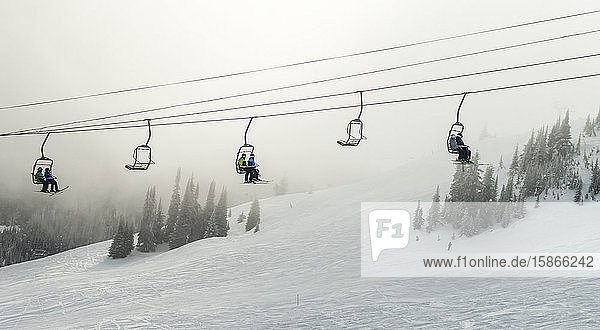Downhill skiers ride on a chairlift through the clouds  Sun Peaks Resort; Sun Peaks  British Columbia  Canada