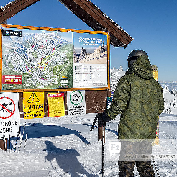 Downhill skiier looking at information board and map at Sun Peaks Resort; Sun Peaks  British Columbia  Canada