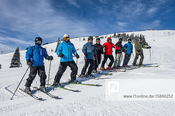 Downhill skiers standing in a row posing for the camera on a snowy slope; British Columbia  Canada