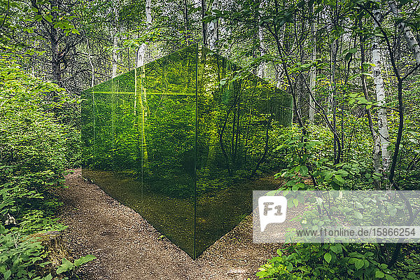 Art installation of green glass walls in a forest  Reford Gardens; Price  Quebec  Canada