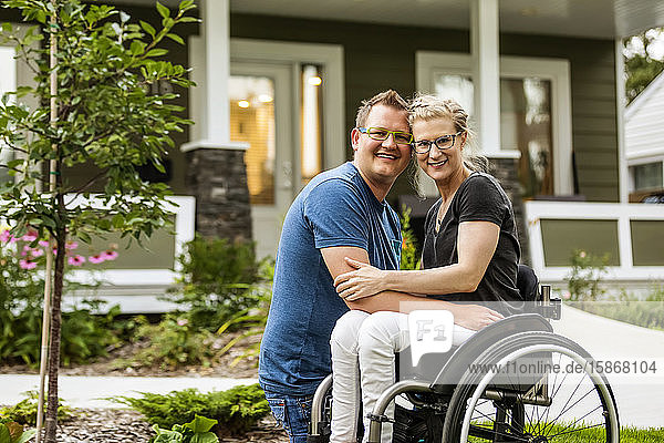A husband and his paraplegic wife posing for a family photo in their front yard on a warm fall day: Edmonton  Alberta  Canada