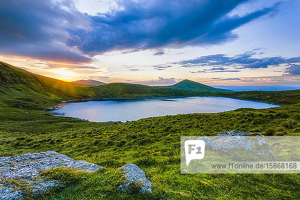 Sun setting over Lough Muskery in the Galty Mountains in summer with large boulders in the foreground  Galty Mountains; County Limerick  Ireland