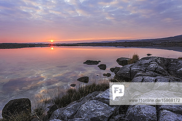Sun setting over lake with reflections on a cloudy evening with limestone rocks with cracks on the shore in the foreground  Burren National Park; County Clare  Ireland