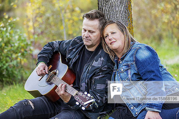 A mature couple spending quality time together and the wife is listening to her husband singing and playing his guitar while in a city park on a warm fall evening: Edmonton  Alberta  Canada