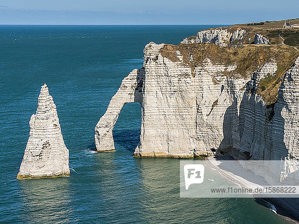 Natural arch in the chalk cliffs with teal coloured water along the coast  Etretat Chalk Complex; Etretat  Normandy  France