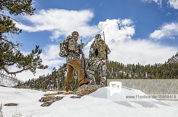 Hunters with camouflage clothing and rifle looking out to a forest; Denver  Colorado  United States of America