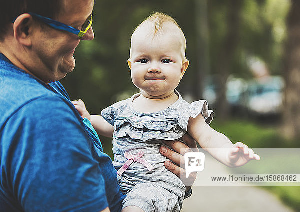 A father holding his baby girl outdoors on a warm fall evening; Edmonton  Alberta  Canada