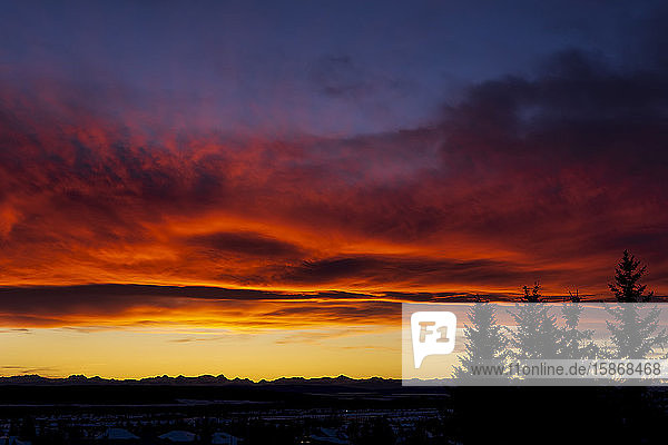 Dramatic colourful sky/clouds at sunset with silhouette trees and mountain range in background; Calgary  Alberta  Canada