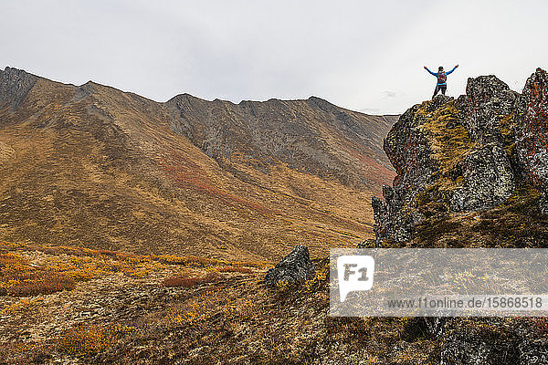 Woman exploring the mountains along the Dempster Highway during autumn in the autumn; Yukon,  Canada