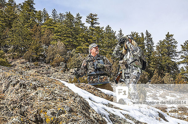 Hunters with camouflage clothing and rifle looking out with binoculars; Denver  Colorado  United States of America