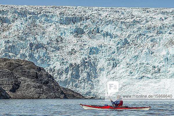 Kayaker in front of a tidewater glacier in Prince William Sound; Alaska  United States of America