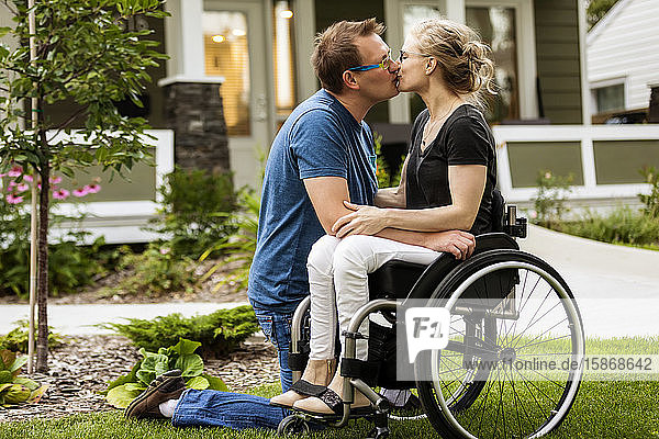 A husband and his paraplegic wife kissing in their front yard on a warm fall day: Edmonton  Alberta  Canada