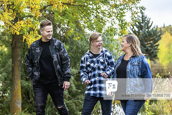 A young man with Down Syndrome walking with his father and mother while enjoying each other's company in a city park on a warm fall evening: Edmonton,  Alberta,  Canada