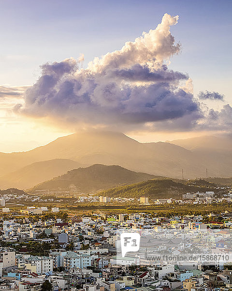 Glowing sunset over the mountains and cityscape of Nha Trang;  with a large cloud formation sitting over the mountains; Nha Trang  Khanh Hoa Province  Vietnam