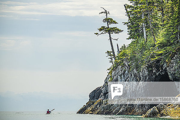 Kayaker paddling through the calm waters in the beautiful scenery of Prince William Sound; Alaska  United States of America
