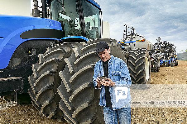 Farmer using a smart phone while standing on a farm beside equipment; Alberta  Canada
