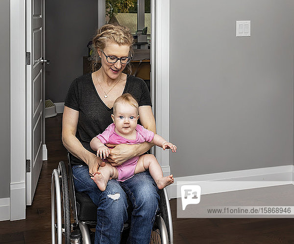 A paraplegic mother holding her baby on her lap while moving around her home in a wheel chair:: Edmonton  Alberta  Canada