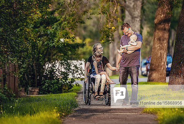A family out walking in the evening and the mother is a paraplegic in a wheelchair; Edmonton  Alberta  Canada