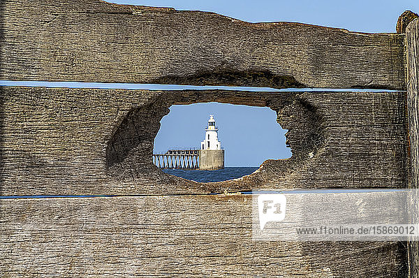 Lighthouse at the end of a pier viewed through a hole in a weathered wooden fence; Blyth  Northumberland  England