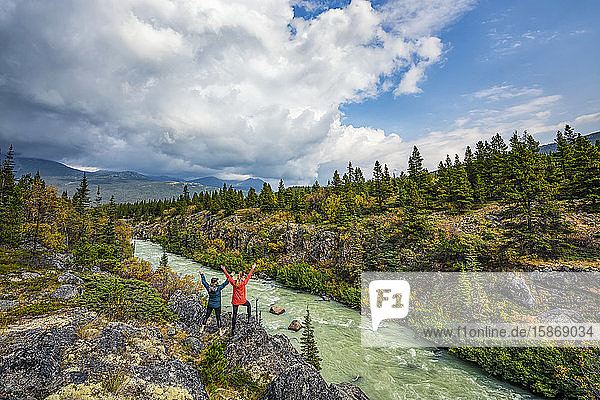 Two women standing overlooking the Tutshi River near the Yukon/British Columbia border; Yukon  Canada