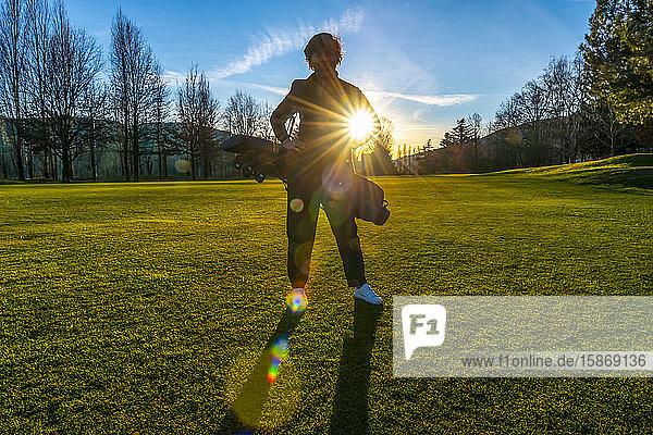 Female golfer backlit by sunlight; Switzerland