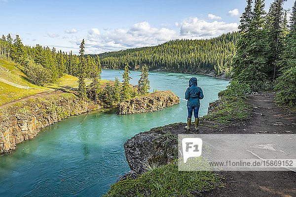 Woman standing above Miles Canyon looking on as the Yukon River flows by; Whitehorse  Yukon  Canada