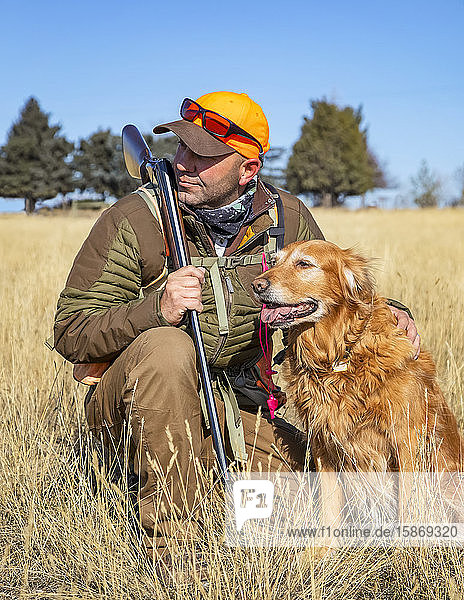 Man hunting with his dog; Denver  Colorado  United States of America