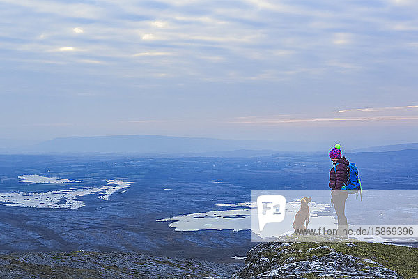 Lone woman hiker with knit hat and dog looking at each other on a cliff edge overlooking lakes in the distance on a cloudy evening in winter  Burren National Park; County Clare  Ireland