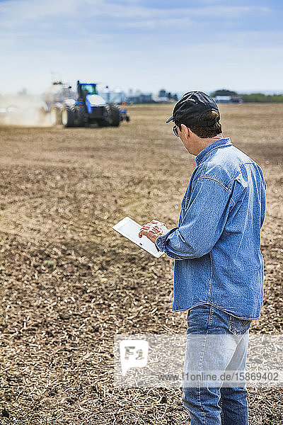 Farmer using a tablet while standing on a farm field and a tractor and equipment seeds the field; Alberta  Canada
