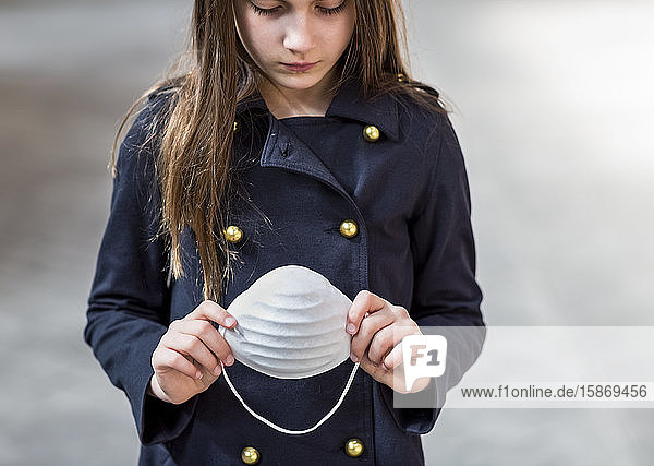 Young girl stands holding protective mask in her hands during the Coronavirus World Pandemic; Toronto  Ontario  Canada